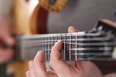 弹经典形状电吉他的男性胳膊 免版税库存照片