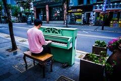 弹绿色色的钢琴的钢琴演奏家 免版税库存照片