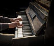 弹老钢琴的人的手 免版税库存图片