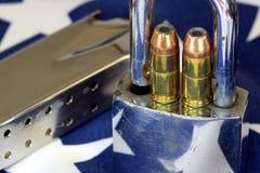 弹药和挂锁在美国旗子-开枪权利和枪枝管制概念 图库摄影