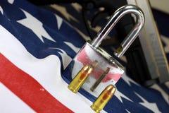 弹药和挂锁在美国旗子-开枪权利和枪枝管制概念 免版税库存照片