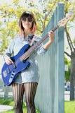 弹蓝色低音吉他的少妇外面 库存照片