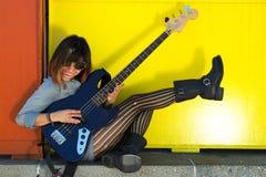 弹蓝色吉他,笑和踢腿的妇女 图库摄影