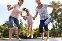 弹起在绷床的祖母、孙女和母亲 免版税库存照片