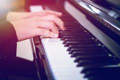 弹钢琴有轻的日落背景的迷离 免版税图库摄影