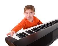 弹钢琴的一个小的小女孩。 免版税库存照片