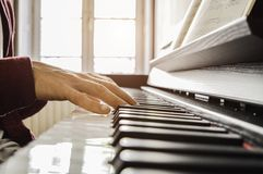 弹钢琴的一个年轻人的手读比分在阳光 库存图片