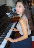 弹钢琴的亚洲女性秀丽 图库摄影