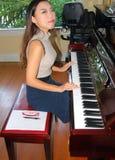 弹钢琴的亚洲女性秀丽 免版税库存图片