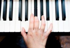 弹钢琴的亚洲妇女` s手 免版税图库摄影