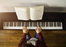 弹钢琴的年轻可爱的人读比分在阳光 免版税库存图片