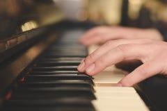 弹钢琴(特写镜头)与oldschool葡萄酒instagram过滤器的手 免版税库存照片