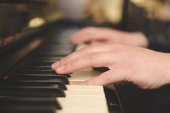 弹钢琴(特写镜头)与oldschool葡萄酒instagram过滤器的手 免版税库存图片