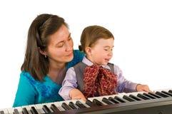 弹钢琴的一个小小男孩。 免版税库存图片