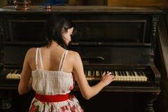 弹钢琴的一个少妇的图片的关闭 免版税库存照片