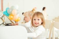 弹钢琴的两个逗人喜爱的小女孩在演播室 库存照片