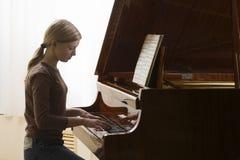 弹钢琴的女孩 免版税图库摄影