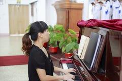 弹钢琴的妇女在教会里 免版税库存图片