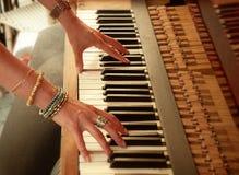 弹钢琴的妇女的手 免版税库存照片