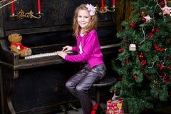弹钢琴的愉快的小女孩 免版税库存照片