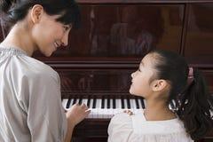 弹钢琴的母亲和女儿 免版税库存图片