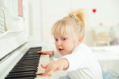 弹钢琴的逗人喜爱的儿童女孩在演播室 库存图片