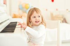 弹钢琴的逗人喜爱的小女孩在轻的屋子里 免版税库存照片