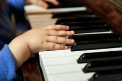 弹钢琴的婴孩手 免版税图库摄影
