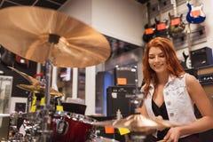弹铙钹的微笑的音乐家在音乐商店 免版税库存照片
