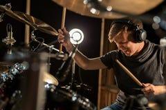 弹鼓和铙钹的男性音乐家在音乐会 图库摄影