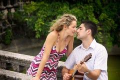 弹他的妇女的人吉他 免版税库存照片