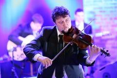 弹他的小提琴的音乐家的特写镜头 免版税库存照片