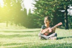 弹ukelele吉他的年轻和愉快的亚裔女孩在公园在晴朗的早晨,当看复制空间时 库存图片