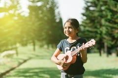 弹ukelele吉他的年轻和愉快的亚裔女孩在公园在晴朗的早晨,当看复制空间时 免版税图库摄影