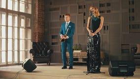 强光礼服和萨克斯管吹奏者的爵士乐歌唱者在阶段的蓝色衣服的 舞蹈 唱歌 影视素材