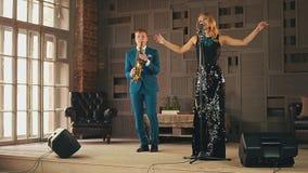 强光礼服和萨克斯管吹奏者的爵士乐歌唱者在阶段的衣服perfrorm的 舞蹈 股票视频