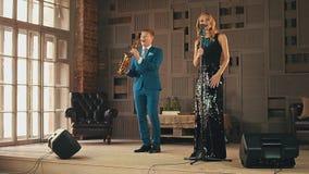 强光礼服的爵士乐歌唱者和萨克斯管吹奏者在阶段执行 减速火箭的样式 影视素材