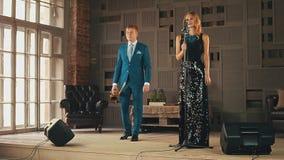 强光礼服的爵士乐歌唱者,蓝色衣服的萨克斯管吹奏者准备执行 微笑 股票视频