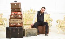 强壮男子典雅在严密的面孔坐疲乏的近的堆葡萄酒手提箱 人、男管家有胡子的和髭交付 库存图片
