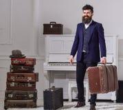 强壮男子典雅在微笑的面孔站立近的堆葡萄酒手提箱,拿着手提箱 人,有胡子的旅行家和 免版税库存图片