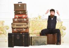 强壮男子典雅在惊奇的面孔坐冲击在堆葡萄酒手提箱附近 行李和拆迁概念 人,男管家 免版税库存图片