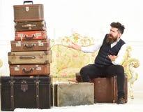 强壮男子典雅在惊奇的面孔坐冲击在堆葡萄酒手提箱附近 行李和旅行的概念 人,男管家 图库摄影