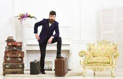 强壮男子典雅在站立近的堆葡萄酒手提箱的周道的面孔 人、旅行家有胡子的和髭与 库存图片