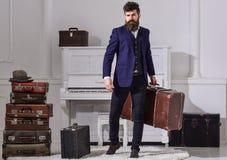 强壮男子时髦在严密的面孔站立并且运载大葡萄酒手提箱 人、旅行家有胡子的和髭与 图库摄影