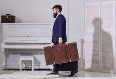强壮男子时髦在严密的面孔走并且运载大葡萄酒手提箱,侧视图 行李和旅行的概念 人 免版税图库摄影