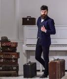 强壮男子时髦在站立近的堆葡萄酒手提箱的周道的面孔 行李和旅行的概念 人,旅行家 免版税图库摄影
