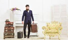 强壮男子有吸引力,典雅在严密的面孔运载葡萄酒手提箱 有胡子的穿着经典衣服的人和髭 免版税库存图片