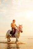 强壮男子的人和马在天空和水背景  男孩方式 库存照片
