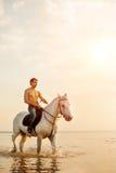 强壮男子的人和马在天空和水背景  男孩方式 图库摄影