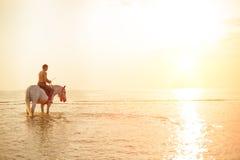 强壮男子的人和马在天空和水背景  男孩方式 免版税库存照片